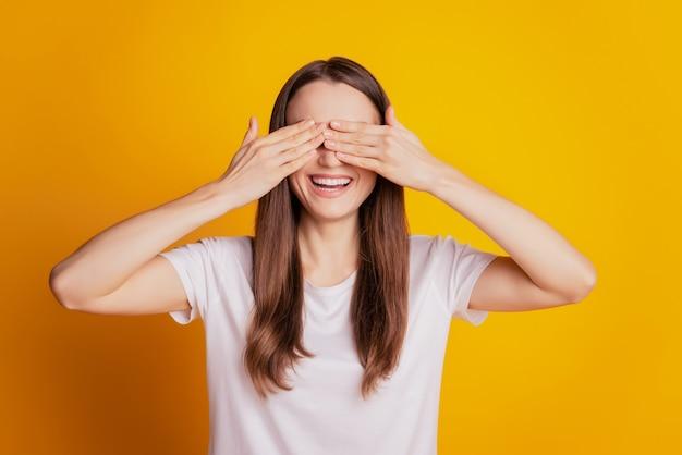 Foto von lustigen überraschten damenhänden, die die augen bedecken, tragen weißes t-shirt, das auf gelbem hintergrund posiert