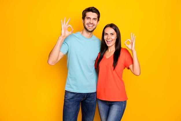 Foto von lustigen zwei personenpaar kerl und dame, die okey symbole zeigen, die übereinstimmung emotional tragen tragen lässig blau orange t-shirts jeans isoliert über gelbe farbe wand