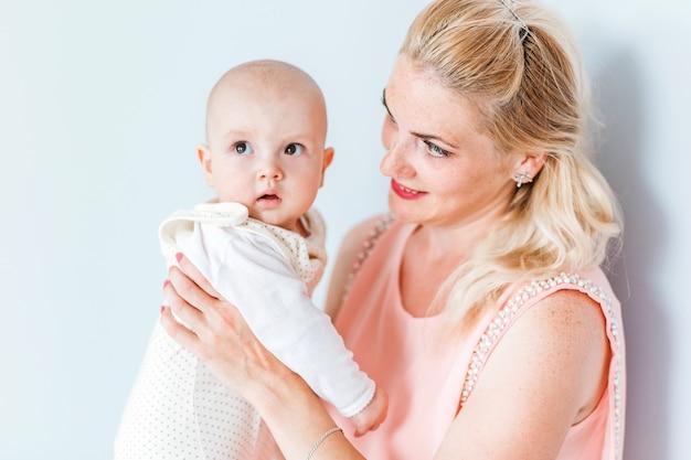 Foto von mutter in einem rosa kleid hält ihren kleinen sohn in ihren armen und lächelt