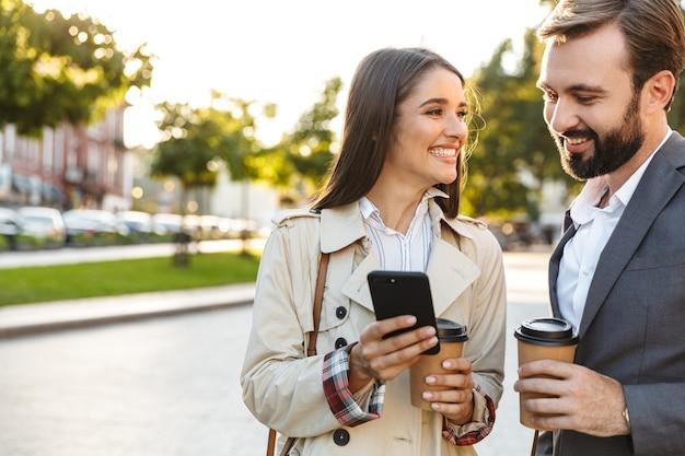 Foto von netten büroangestellten, mann und frau in formeller kleidung, die kaffee zum mitnehmen halten, während sie das handy auf der stadtstraße benutzen?