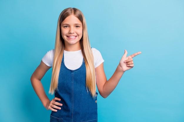 Foto von netten optimistischen teenager blonden langen haaren mädchen zeigen leeren raum tragen weißes t-shirt jeanskleid isoliert über blauem hintergrund