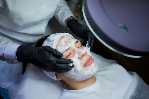 Foto von oben schließen von den händen der kosmetikerin rollt peeling auf.