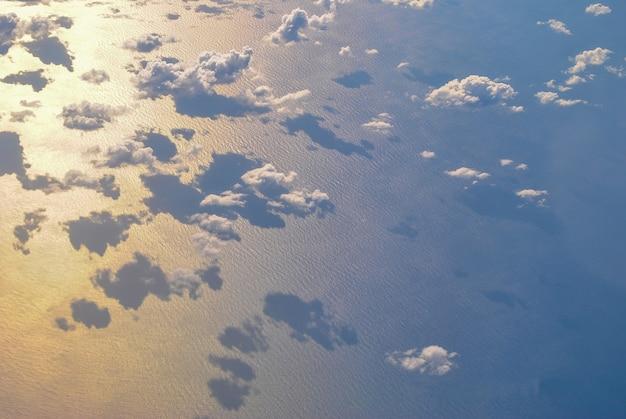 Foto von oben über den wolken aufgenommen. unter den wolken ist das meer. wolken spiegeln sich im meer