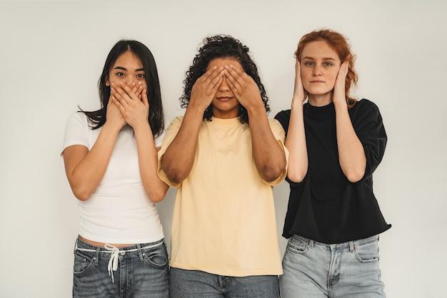 Foto von optimistischen fröhlichen jungen frauen, gemischtrassigen freunden. nachahmen sehen nichts böses, hören nichts böses, sprechen nichts böses.