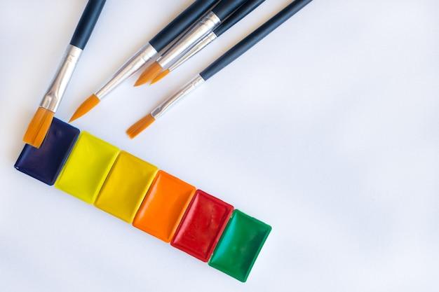 Foto von pinseln für aquarellmalerei nah oben und satz aquarellfarben in den küvetten