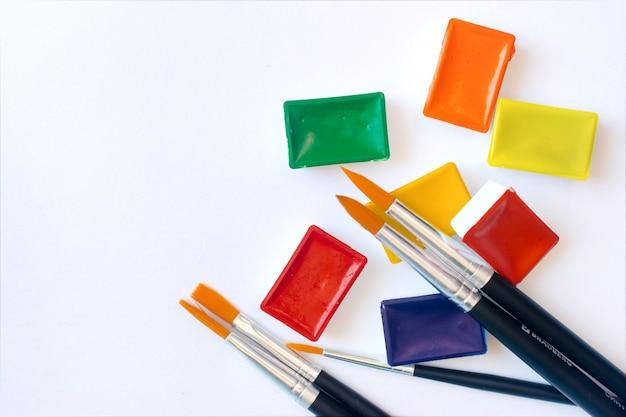 Foto von pinseln für aquarellmalerei nah oben und satz aquarellfarben