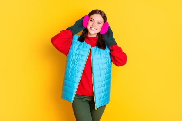 Foto von positivem, fröhlichem, charmantem mädchen genießen winter-kältewetter-wochenende berühren ohrenschützer genießen saison-outfit einzeln auf lebendigem farbhintergrund