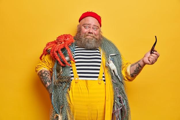 Foto von positiven bootsmann posiert mit ocotpus, genießt meereslebewesen, verbringt viel zeit am boot zusammen mit der ganzen besatzung, hält pfeife