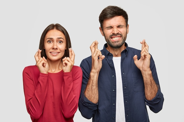 Foto von positiven weiblichen und männlichen kreuzfingern für viel glück vor einem wichtigen ereignis, nebeneinander stehen, wünschenswerte blicke haben, in lässigem outfit gekleidet, isoliert über weißer wand.