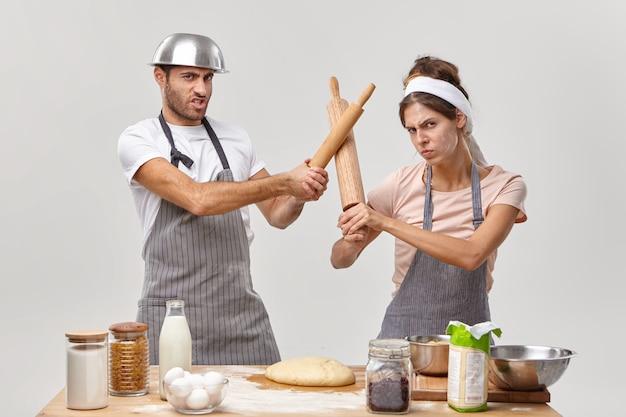 Foto von professionellen köchen haben kampf in der küche, nehmen an kulinarischen wettbewerben teil, fechten mit nudelhölzern, bereiten frischen teig zum backen von kuchen vor, machen keksdessert. kochwettbewerb, wer am besten ist