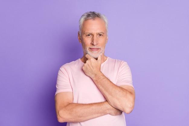 Foto von rentner alter mann hand kinn grübeln blick kamera tragen rosa t-shirt isoliert violetter farbhintergrund