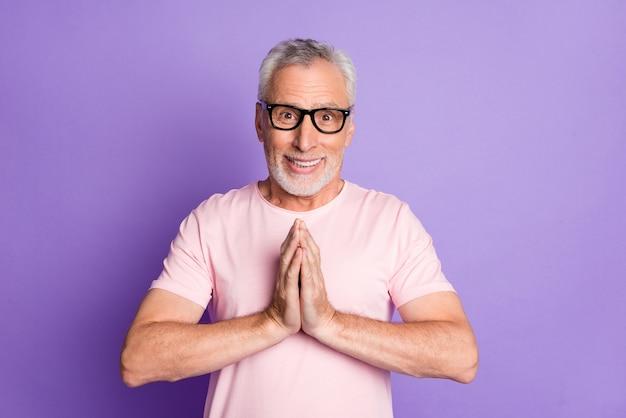 Foto von rentner opa halten hände plädieren blick kamera tragen brillen rosa t-shirt isoliert violetter farbhintergrund