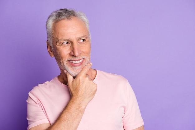 Foto von rentner opa hand kinn glänzendes lächeln blick seite leerer raum tragen rosa t-shirt isoliert violetter farbhintergrund