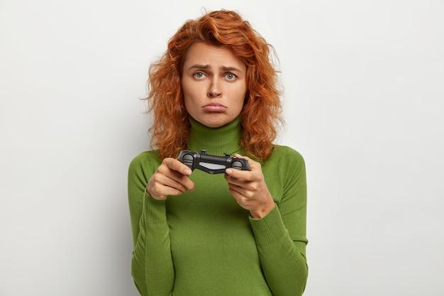 Foto von rothaarigen teenager-mädchen mit joystick spielen, hat unglücklichen ausdruck, verliert videospiel, verbringt freizeit zu hause, echte spieler zu sein. menschen, freizeit, unterhaltungskonzept