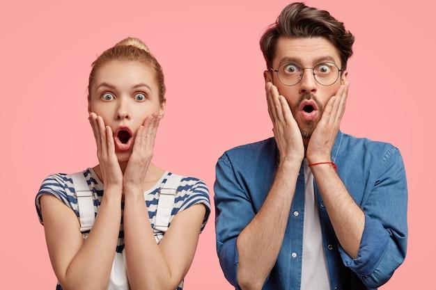 Foto von schockierten stilvollen gruppenmitgliedern berühren wangen mit beiden händen, blicken mit erstaunen direkt, hören entsetzte nachrichten, erhalten prüfungsergebnis, modell gegen rosa wand
