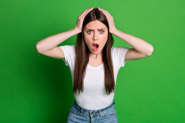 Foto von schockierter frau gekleidet lässiges outfit arme kopf offener mund isoliert grüner hintergrund