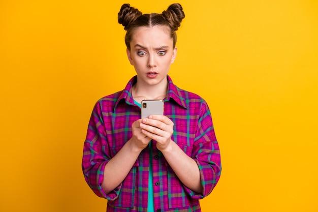 Foto von schockierter teenager-dame zwei brötchen schauen telefon lesen kommentare blog quarantäne schlechte nachrichten sprachlos stupor tragen lässig kariertes hemd isoliert gelb heller farbhintergrund