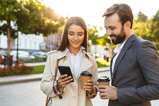 Foto von schönen büroangestellten, mann und frau in formeller kleidung, die kaffee zum mitnehmen halten, während sie das handy auf der stadtstraße benutzen using
