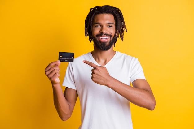Foto von schwarzem bart dreadlocks kerl zeigt finger halten kreditkarte tragen weißes t-shirt isoliert gelber hintergrund