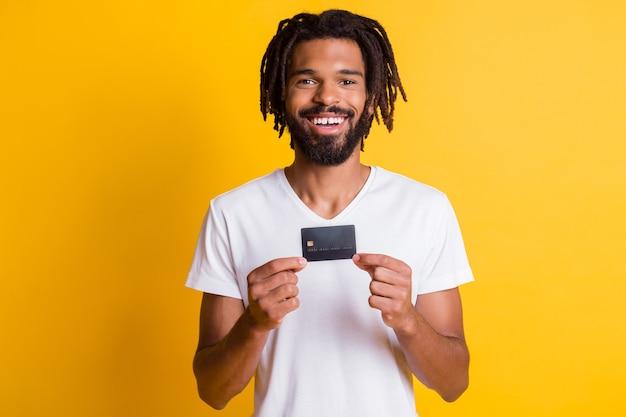 Foto von schwarzem kerl halten debitkarten-look kamera tragen weißes t-shirt isoliert gelber hintergrund