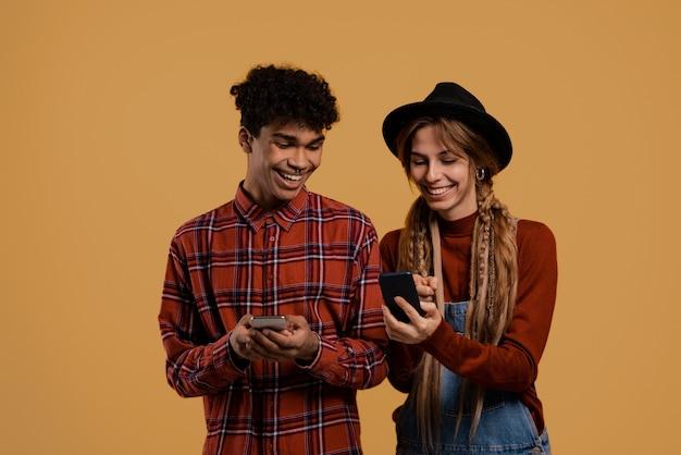 Foto von schwarzen männlichen und weißen weiblichen bauern beobachten ihre smartphones. mann trägt kariertes hemd, frau trägt jeans insgesamt und hat isolierten braunen farbhintergrund.
