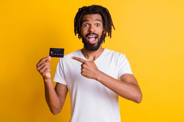 Foto von schwarzen, stilvollen dreadlocks mit direktem zeigefinger halten kreditkarte mit offenem mund tragen weißes t-shirt isoliert gelber farbhintergrund