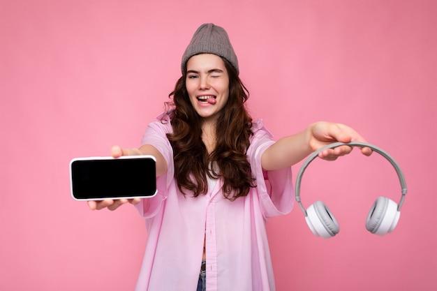 Foto von sexy hübscher positiver junger brünetter lockiger frau mit rosa hemd und grauem hut isoliert