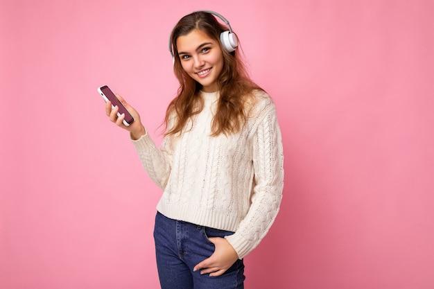 Foto von sexy positiver schöner junger frau, die einen hellweißen, stylischen pullover trägt, isoliert auf rosa