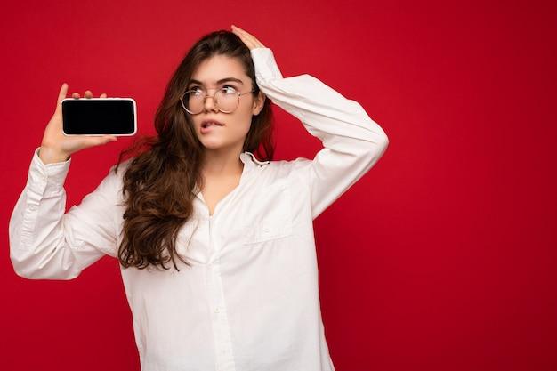 Foto von sexy schöne junge brünette frau mit weißem hemd und optischer brille isoliert über