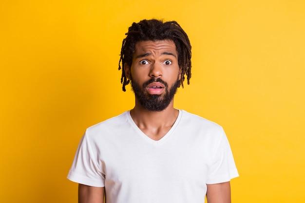 Foto von starren dunklen hauttypen mit offenem mund hören unerwartete schreckliche nachrichten tragen lässiges t-shirt isoliert gelber hintergrund