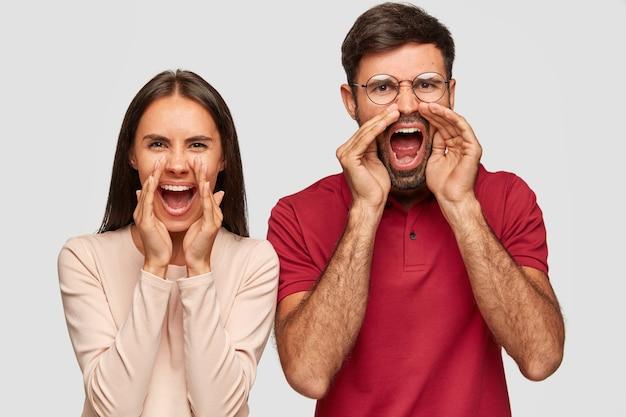 Foto von stressigen europäischen frau und mann rufen laut aus, halten den mund weit offen, schreien vor wut jemanden an