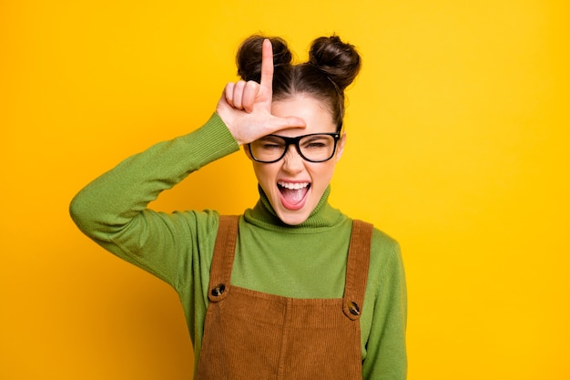 Foto von student lady stimmung grimasse zeigen verlierer symbol stirn isoliert gelber hintergrund