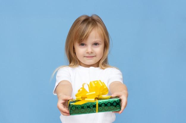Foto von süßen süßen schulmädchen trägt weißes t-shirt lächelnd mit gelber und grüner geschenkbox isoliert blauer hintergrund