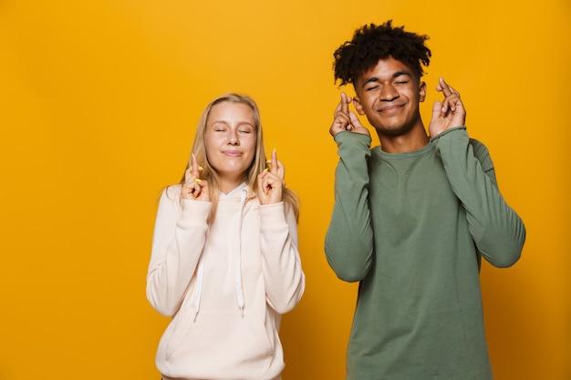 Foto von teenager-freunden, mann und frau 16-18, die die daumen drücken und nach glück träumen, isoliert auf gelbem hintergrund