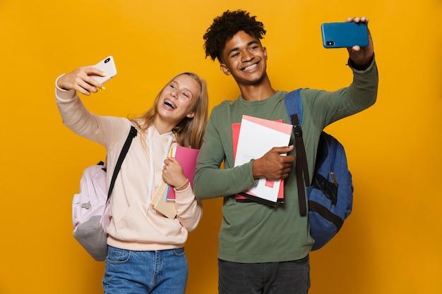 Foto von teenager-studenten, mann und frau 16-18, die rucksäcke tragen, die selfie auf mobiltelefonen machen und schulhefte halten, einzeln auf gelbem hintergrund