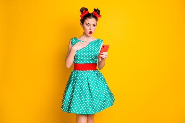 Foto von traurigen mädchen blogger verwenden smartphone tragen grün-rote kleidung isoliert hell glänzenden farbhintergrund