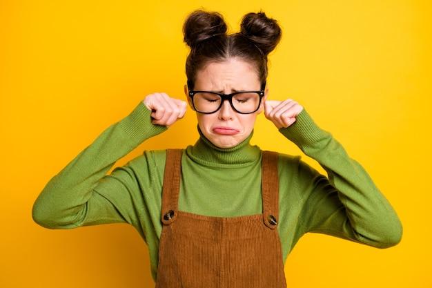 Foto von trauriger trauriger lady geek nerd studentin weint tränen isoliert auf gelbem hintergrund