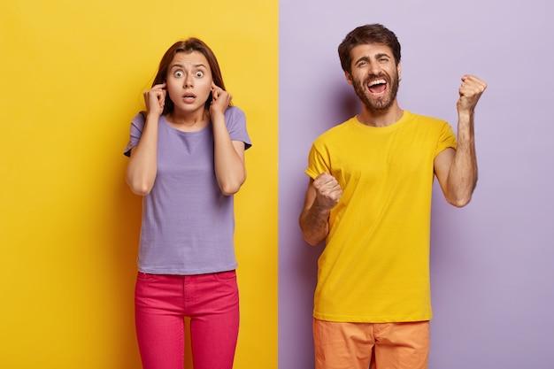 Foto von überraschten weiblichen steckern ohren, schockiert von lärm, froh mann geballt fäuste