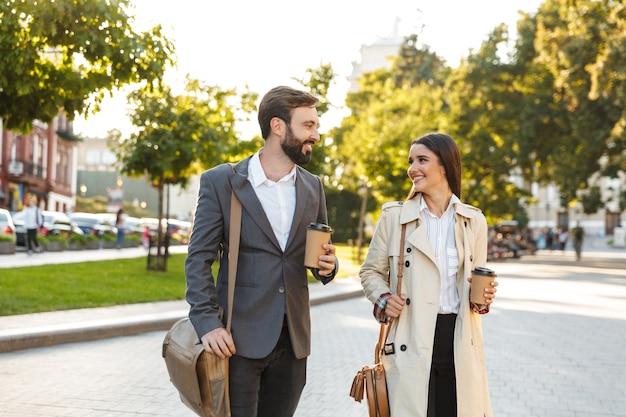 Foto von umgänglichen büroangestellten, mann und frau in formeller kleidung, die kaffee zum mitnehmen halten, während sie auf der stadtstraße gehen?