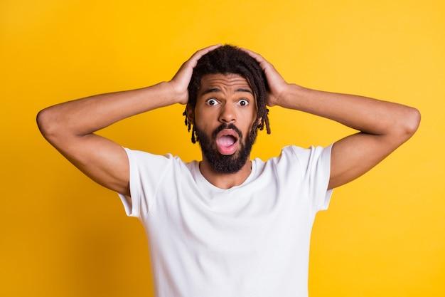 Foto von verängstigtem mann mit dunkler haut mit offenem mund schreckliche nachrichten arme auf dem kopf tragen t-shirt isoliert gelber hintergrund