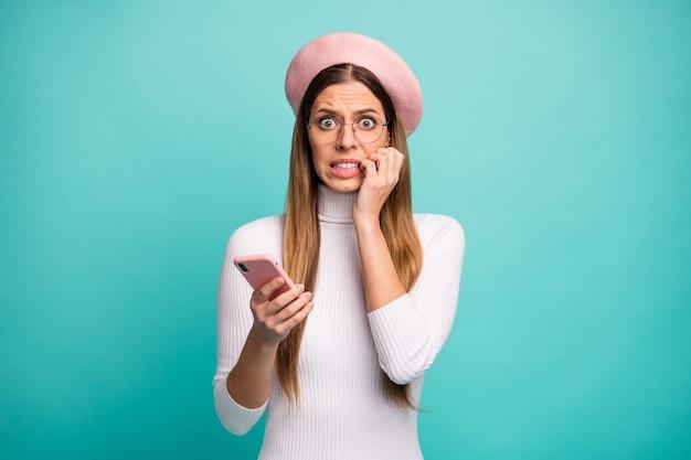 Foto von verängstigter freiberuflicher dame, die telefon hält, negative kommentare lesen, die finger beißen, tragen spezifikationen moderne rosa baskenmütze weißer rollkragen isoliert hellblaugrüner farbhintergrund