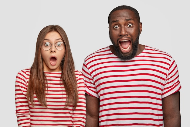 Foto von verblüfften jungen partnern oder kollegen gemischter rassen starren mit herausgesprungenen augen und weit geöffnetem mund