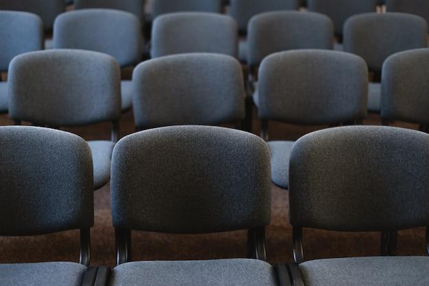 Foto von vielen stühlen in hübschem publikum, bei einer veranstaltung
