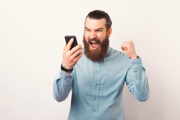 Foto von wütendem bärtigem geschäftsmann, der am smartphone schreit