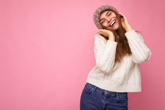 Foto von ziemlich positiver amüsanter junger brünetter frau, die über rosa hintergrundwand isoliert ist