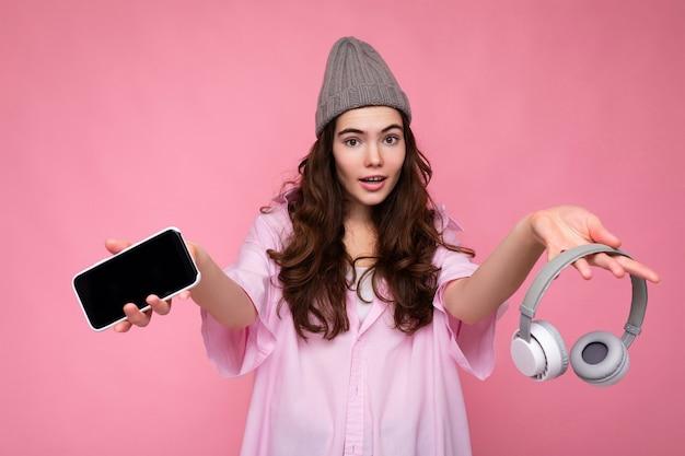 Foto von ziemlich positiver junger brünetter lockiger frau mit rosa hemd und grauem hut isoliert über