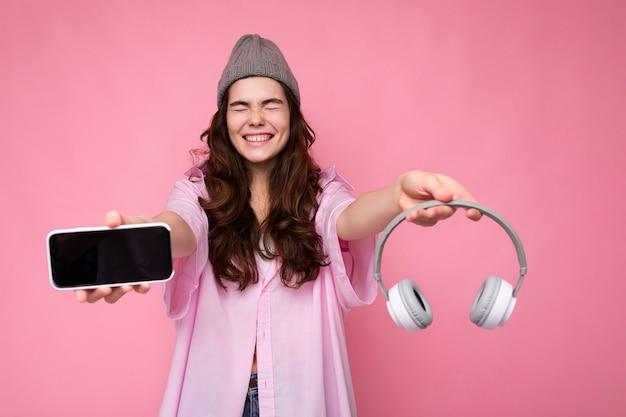 Foto von ziemlich positiver lachender junger brünetter lockiger frau mit rosa hemd und grauem hut