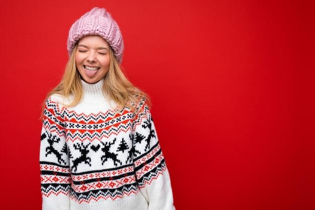 Foto von ziemlich positiver, lustiger lächelnder junger blonder frau, die über roter hintergrundwand isoliert ist und einen winterpullover und einen rosa hut trägt, der zunge zeigt und spaß hat