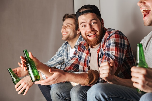 Foto von zufriedenen junggesellen, die glücklich schreien, während sie zu hause feiern und fußballspiel mit bier trinken beobachten