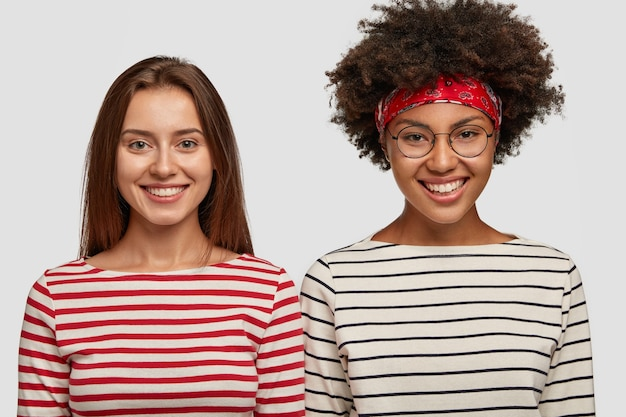 Foto von zufriedenen multiethnischen frauen in gestreiften pullovern